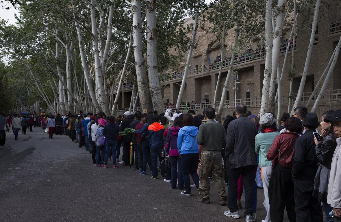 相較於北京故宮每年近1,700萬人次的遊客數量,敦煌一年只有170萬遊客可以進場,原因是為了保護珍貴文物而限制參觀人流;但每年慕名而來的遊客還是絡繹不絕。(圖片來源:Getty)