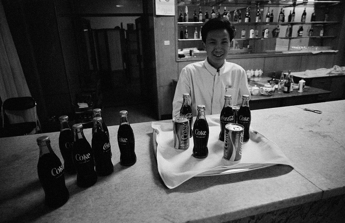 1979年2月,可口可樂進入中國市場不久,一名酒吧侍應把瓶瓶罐罐可樂排列,吸引客人購買。(圖片來源:Getty)