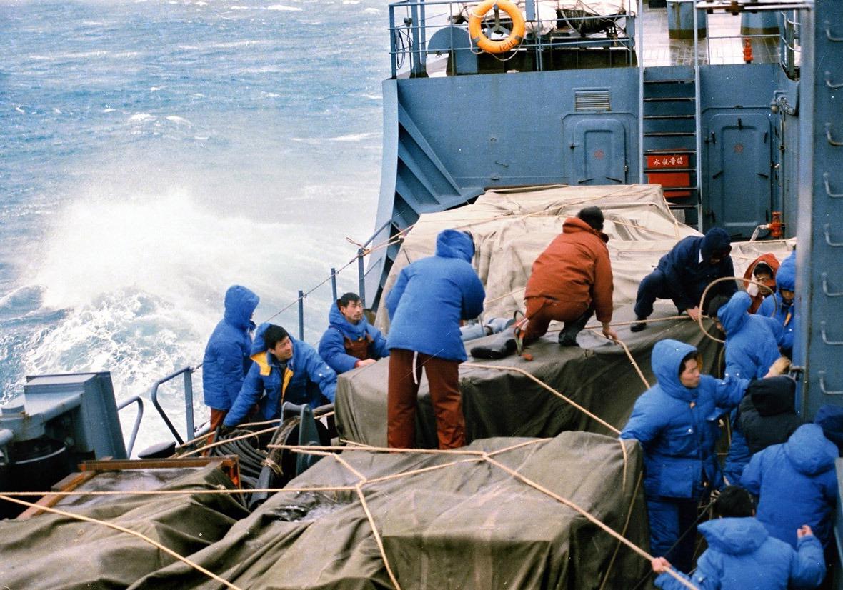 考察隊在驚濤駭浪中忙著用繩索固定建站物資。