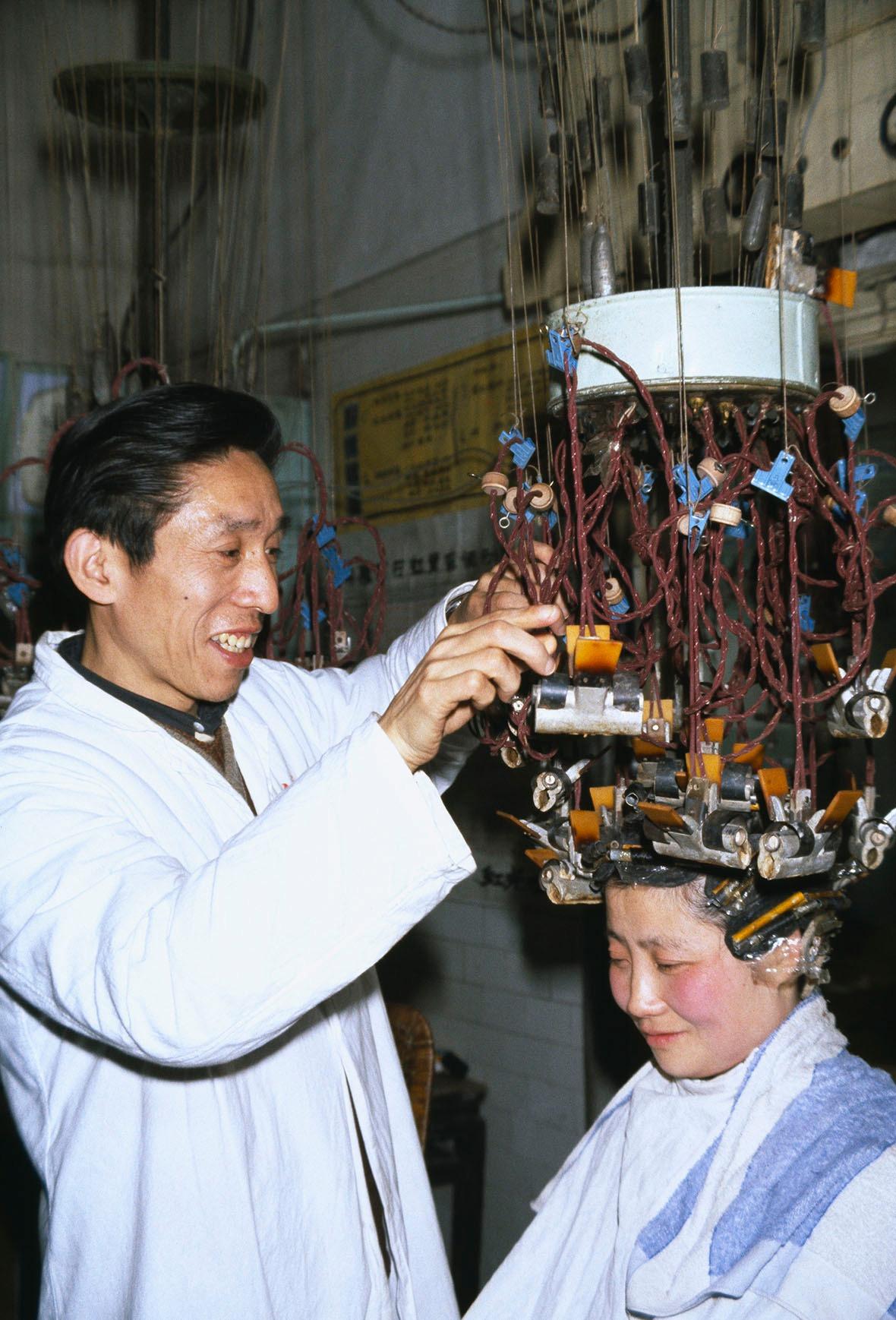 1979年中國,笑容可掬的髮型師在顧客頭上夾滿燙髮夾。