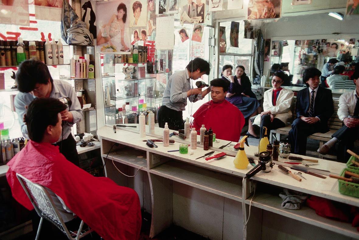 1989年一間髮廊裏,髮型師細心用風筒為顧客吹起「飛機頭」。髮廊生意很好,鏡子展示後排坐滿輪候理髮的客人。