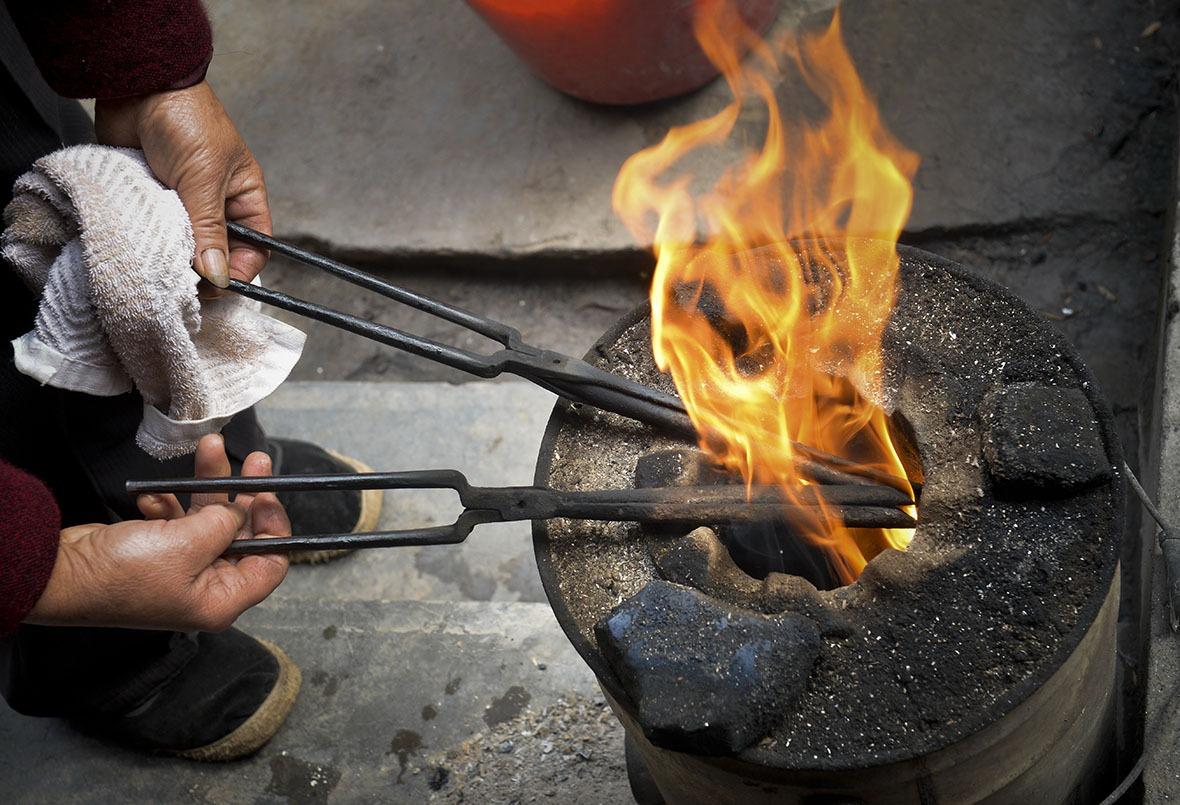 用火鉗燙髮,先要把鉗子放進火堆加熱。