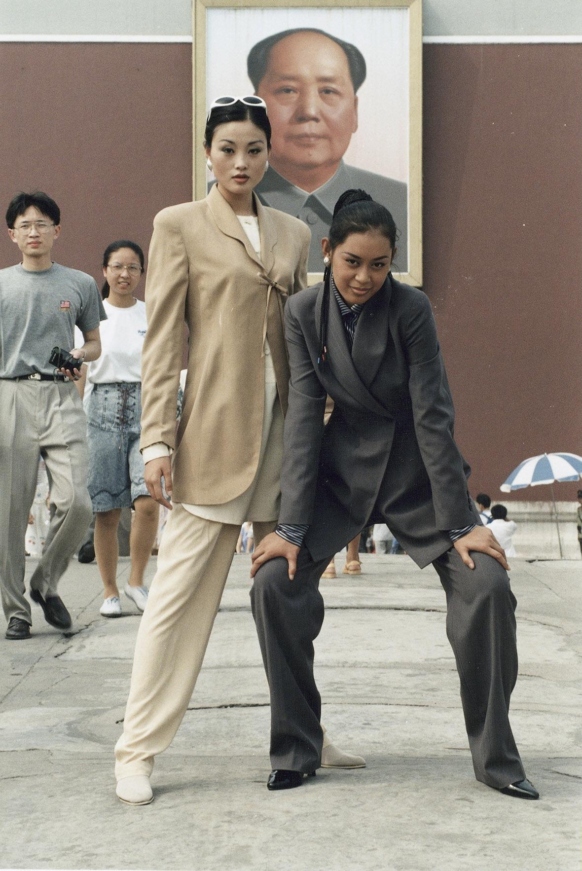 兩名模特兒穿上米色和灰色的休閒西褲套裝,在毛澤東的畫像前擺甫士。