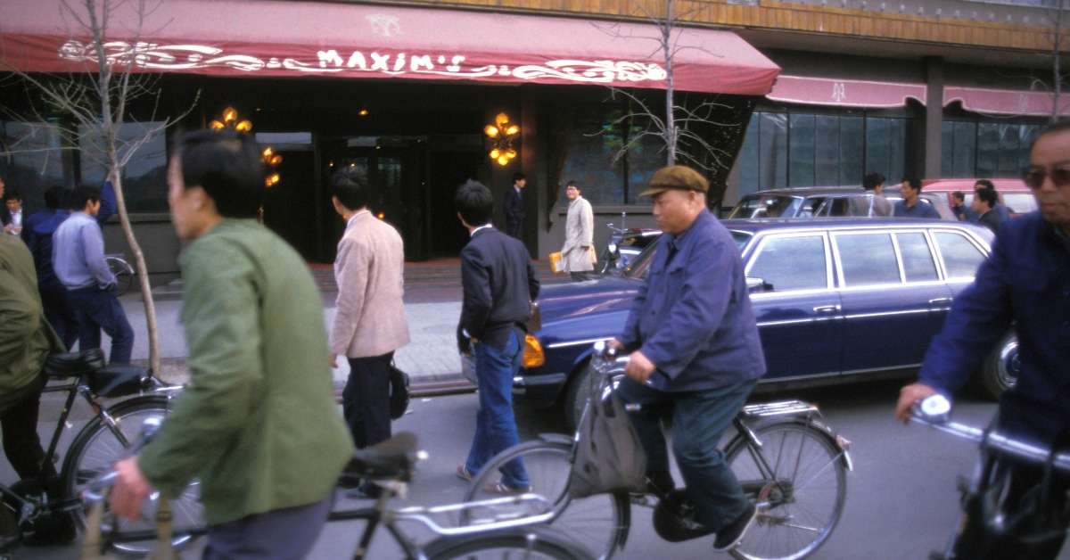 圖為1985年北京。此時全國第一間西餐廳、馬克西姆餐廳(Maxim's)已開業兩年。在北京街頭上,部分人脫去藍綠色的制服,換上個性化的西裝襯衣,他們經過時,不自覺偷望餐廳幾眼。