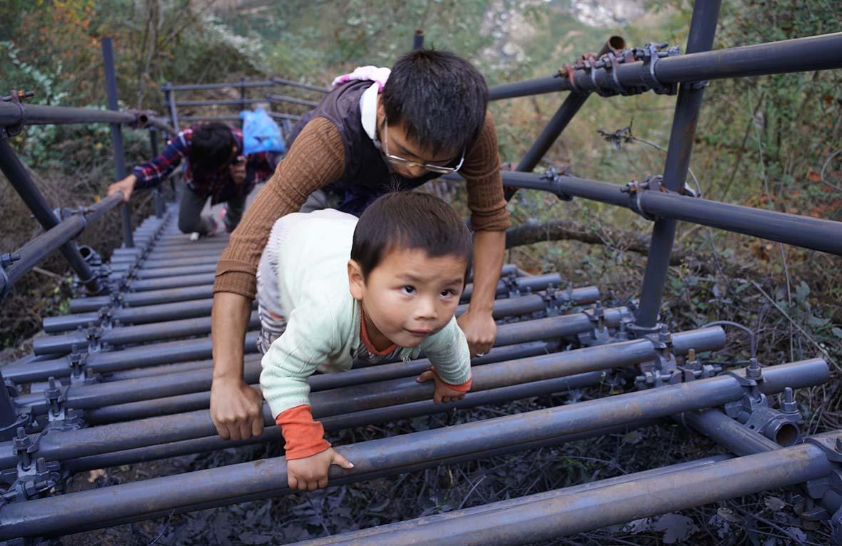 鋼梯建成後,勒爾小學的老師帶着3歲的兒子跟着學生爬梯上懸崖村家訪。過去路不好走,他從未帶過兒子上山。