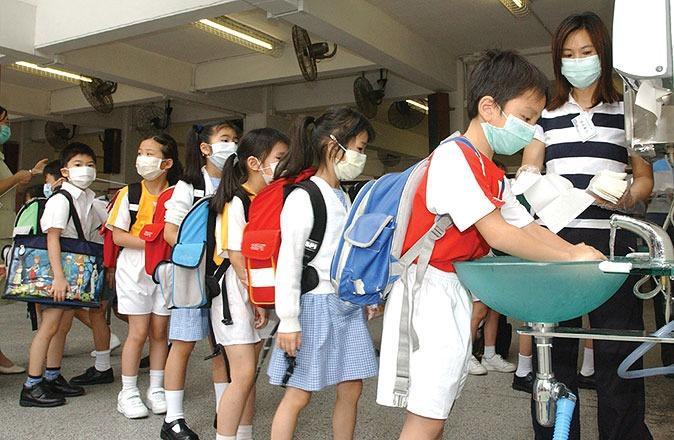 2003年3月沙士爆發,政府在3月29日宣布中小學等停課。5月12日起學生分階段復課,學生須佩戴口罩上課,經常洗手。(圖片來源:政府年報)