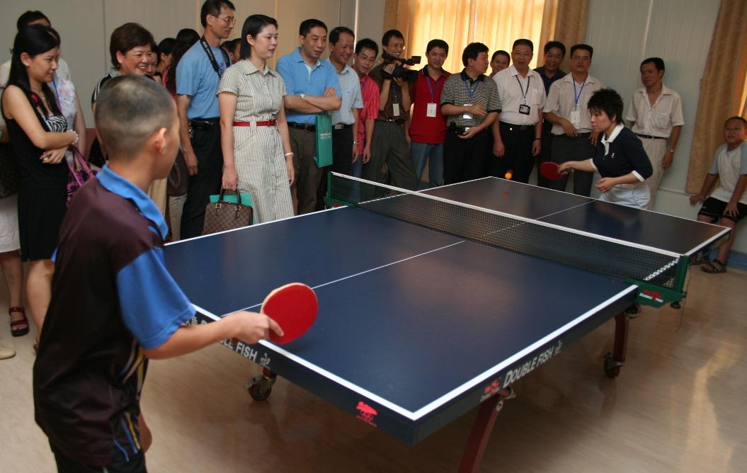 鄧亞萍探訪醫院時與職工及小朋友過招。(圖片來源:人民視覺)