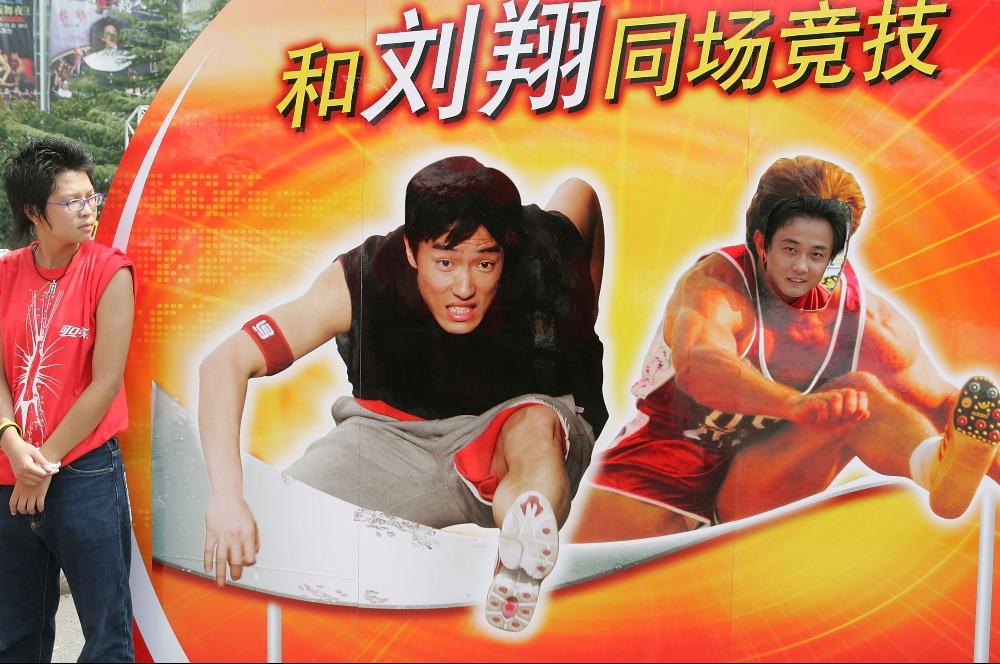 2005年,一名男子在上海體育場的廣告牌上與劉翔「合照」。(圖片來源:Getty)
