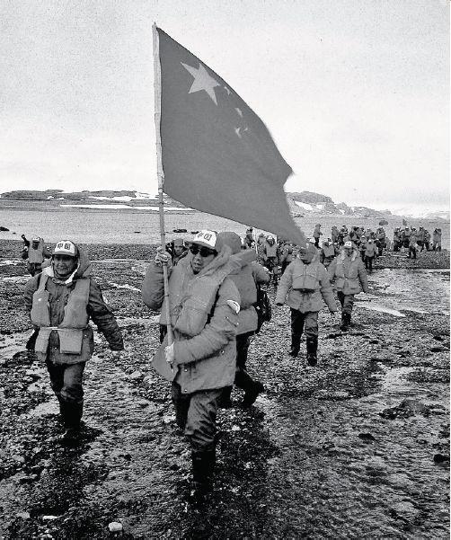 1984年12月,中國南極洲考察隊隊長郭琨高舉五星紅旗,率領隊員登上了南極喬治王島。(網上圖片)