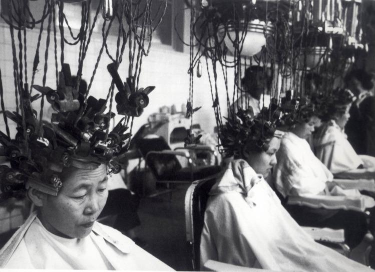 80年代初北京,幾名頭頂燙髮機的客人呈一字型排開,靜候曲髮完成。(圖片來源:中新社)