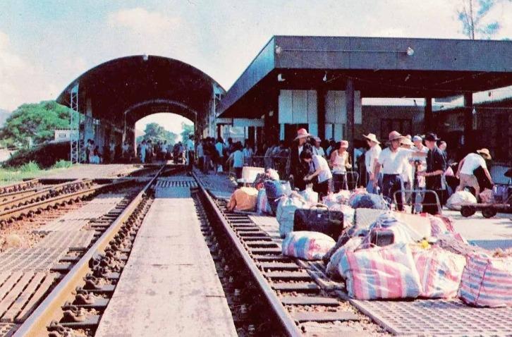80年代羅湖火車站,頭戴草帽、身穿白汗衣的旅客以大包小包的紅白藍袋盛載物品回鄉。